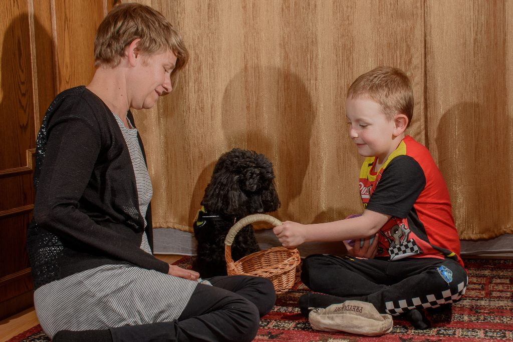 kutyaterápiás foglalkozás, gyerek és szakember a kutyával
